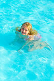 Girl bathes. In pool in blue clear water Royalty Free Stock Photos
