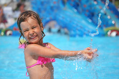 Girl bathes in pool under water splashes. Little girl bathes in pool under water splashes in aquapark Royalty Free Stock Photo