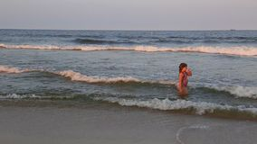 Girl bathes in waves. Cute happy girl floats in the ocean of great waves girl bathes in waves stock footage