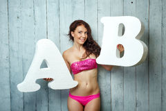 Girl in a bathing and letters Stock Photos