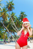 The girl in a bathing suit and a cap of Santa Clau Royalty Free Stock Image