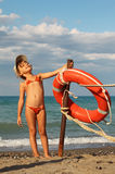 Girl in bathing suit and cap standing on beach. Beautiful little girl in bathing suit and cap standing on beach. she clings to metal pole, on pole hanging red Royalty Free Stock Photo