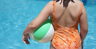 Girl in bathing suit with a colored ball Stock Photos
