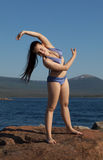 The girl in a bathing suit doing gymnastics on the rock Stock Photo