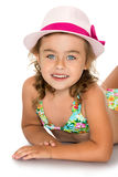 Girl in a bathing suit and hat. Beautiful little blonde girl in a blue swimsuit lying on the floor and smiling at the camera. The head girls pink hat. The plan Stock Photos