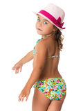 Girl in a bathing suit and hat. Beautiful little girl in the pink hat and the swimsuit turned his back to the camera . Closeup - Isolated on white background Stock Photo