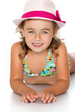 Girl in a bathing suit and hat. Joyful little tanned girl in swimsuit and hat laying on the floor and looking at the camera - Isolated on white background.The Stock Photography