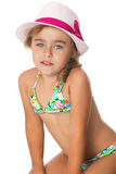 Girl in a bathing suit and hat. Very sweet, adorable little girl in a bathing suit and a pink hat with a red ribbon, looking right at the camera. Closeup Stock Image