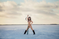 Girl in bathing suit with ice screw on the ice Royalty Free Stock Photo