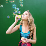 Girl in a bathing suit inflating air bubbles Stock Photo