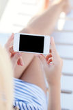 Girl in a bathing suit lying on a chaise lounge with touch phone Stock Image