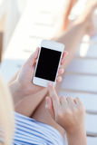 Girl in a bathing suit lying on a chaise lounge with touch phone. Girl in a bathing suit lying on a white chaise lounge with touch phone royalty free stock image
