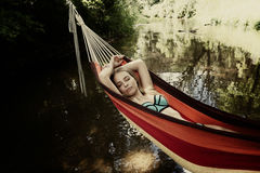 Girl in a bathing suit lying in a hammock over the water Stock Images