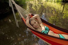 Girl in a bathing suit lying in a hammock over the water Royalty Free Stock Photography