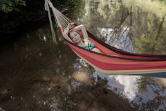 Girl in a bathing suit lying in a hammock over the water Royalty Free Stock Photos