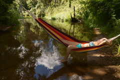 Girl in a bathing suit lying in a hammock over the water Stock Image