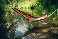 Girl in a bathing suit lying in a hammock over the water Stock Photo
