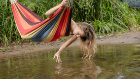 Girl in a bathing suit lying in a hammock over the water Royalty Free Stock Images