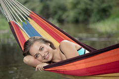 Girl in a bathing suit lying in a hammock over the water Stock Photography
