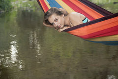 Girl in a bathing suit lying in a hammock over the water Royalty Free Stock Photo