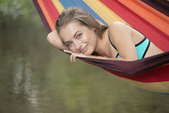 Girl in a bathing suit lying in a hammock over the water Stock Photos