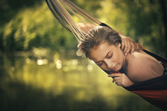 Girl in a bathing suit lying in a hammock over the water Royalty Free Stock Image