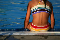 Girl in bathing suit relaxing at the edge of a pool. Closeup view of tan girl in colorful two piece bathing suit sitting on the edge of a pool Stock Images