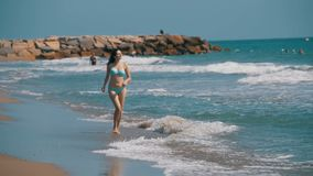 Girl in bathing suit runs along the sea shore at the beach in Slow Motion. Girl in bathing suit runs along the sea shore at the beach. Slow Motion in 96 fps stock footage