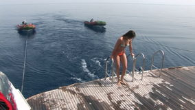 Girl in a bathing suit on a ship near water in Red Sea. Filming a movie. Young girl smiling at camera stock video footage
