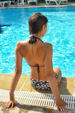 Girl in a bathing suit sits  at the edge of the pool Stock Photo