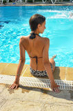 Girl in a bathing suit sits  at the edge of the pool Stock Images
