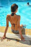 Girl in a bathing suit sits  at the edge of the pool Stock Photography