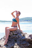 Girl in bathing suit sitting on large stone. On background of blue river Royalty Free Stock Photo