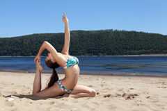 Girl in bathing suit sitting on splits sunny beach royalty free stock images