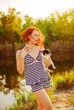 The girl in a bathing suit with a small dog at the lake Stock Photo
