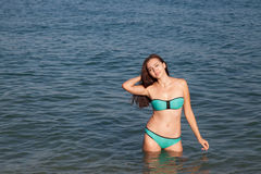 Girl in bathing suit stands in the sea. And tans Royalty Free Stock Images