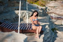 A girl in a bathing suit sunbathes on a deck chair. A woman in a swimsuit sits on a deckchair, sunbathes on the beach, sunbathes.  stock photography