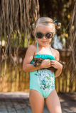 Girl in a bathing suit and sunglasses holding his little kitten and looking at him with love. Girl with a small kitten in her arms Royalty Free Stock Photography
