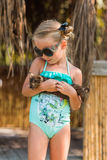 Girl in a bathing suit and sunglasses holding his little kitten and looking at him with love Royalty Free Stock Photography