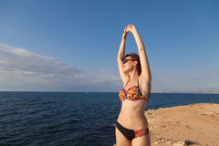 Girl in a bathing suit sunning on the beach Stock Image