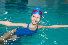 Girl in a bathing suit, swim cap, goggles, holding on. Beautiful girl in a bathing suit, swim cap, goggles, holding on overboard in a swimming pool Royalty Free Stock Image