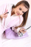 Girl in a bathrobe. Young long-haired blonde girl in a bathrobe , holding lip gloss and mirror Stock Image