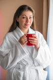 Girl in bathrobe with a cup near the window Royalty Free Stock Photography
