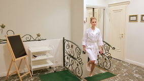Girl in bathrobe goes for cosmetic procedures stock video footage