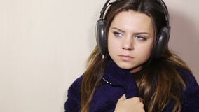 Girl in bathrobe with headphones stock footage