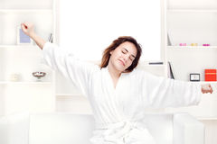 Girl in bathrobe at home stretching arms Royalty Free Stock Image