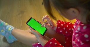 Girl in a bathrobe uses a phone with a green screen trackers