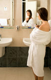 Girl in the bathroom. Girl looking in the mirror in the bathroom Stock Photography