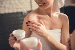 Girl in the bathroom. Beautiful girl in bath towel is applying cream on her shoulder while standing in front of the mirror in bathroom stock photography