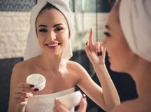 Girl in the bathroom. Beautiful girl in bath towel is applying cream and smiling while looking into the mirror in bathroom stock photo